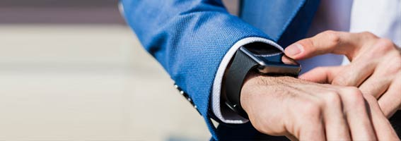 A man in business attire taps a smart watch.
